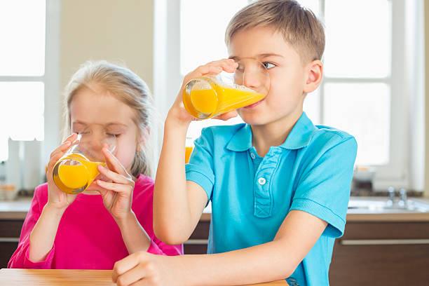 geschwister drinking orange juice in kitchen at home - innocent saft stock-fotos und bilder