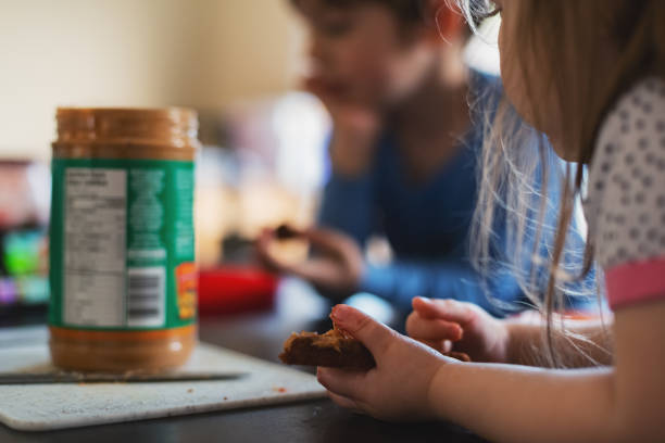 Siblings Eating Lunch Together Brother & sister eat peanut butter & jam sandwiches together. allergy stock pictures, royalty-free photos & images