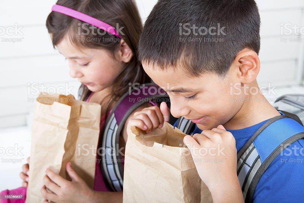 Siblings eating school lunch stock photo