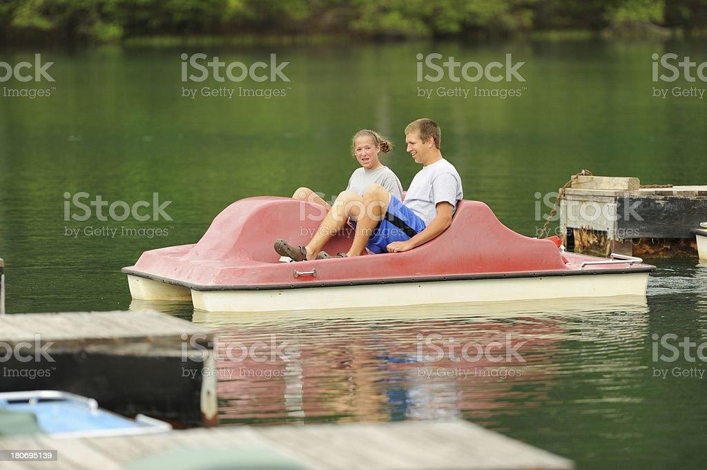 Siblings enjoying pedal boat stock photo