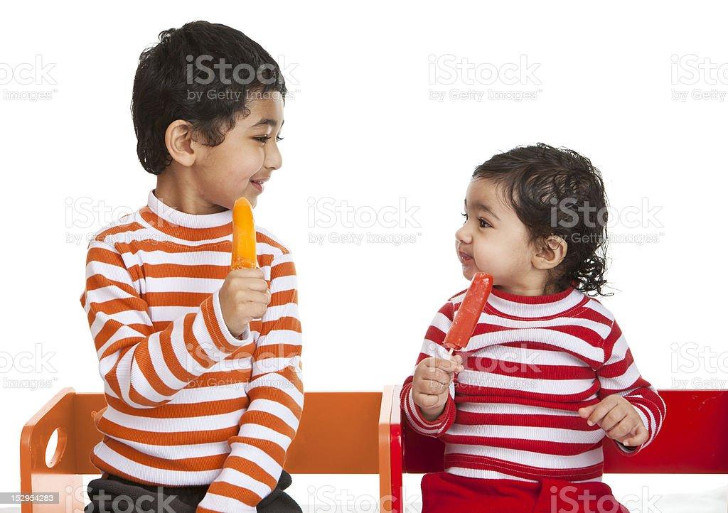 Siblings Enjoying Popsicles stock photo