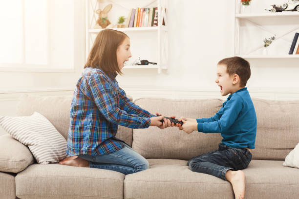 Siblings fighting over remote control at home Siblings fighting over remote control at home, brother and sister have quarrel, copy space sibling stock pictures, royalty-free photos & images