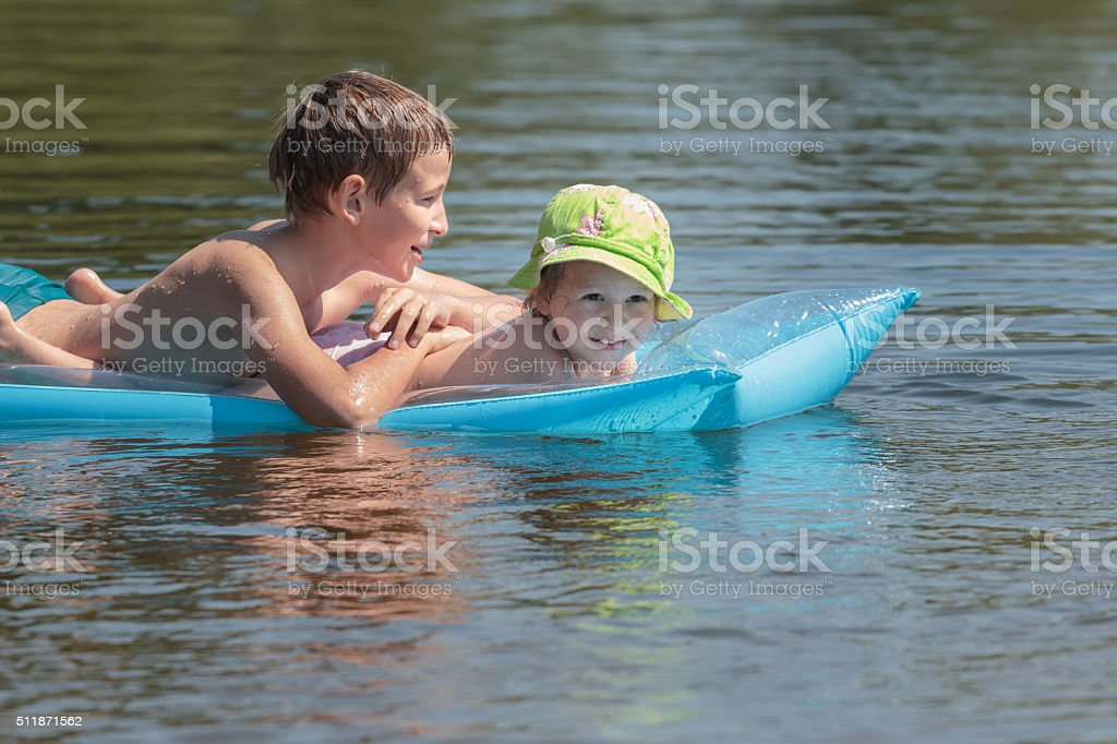 Siblings floating on inflatable pool air mat in summer pond stock photo