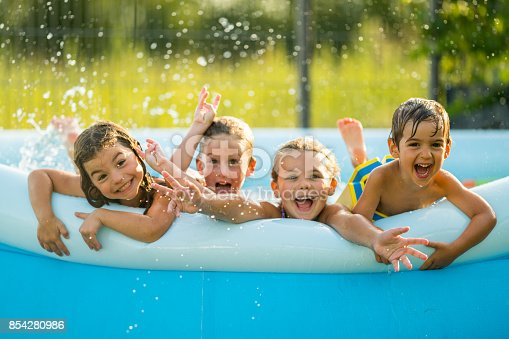 four young children kids siblings at the age of 3, 4 and 6 in blue inflatable swimming wading paddling pool with wet hair laughing smiling enjoying the cooling in heat wave shallow focus water drops giving the feeling of refreshing