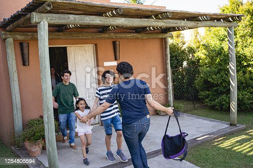 Family greeting at the front door after being apart for a long time