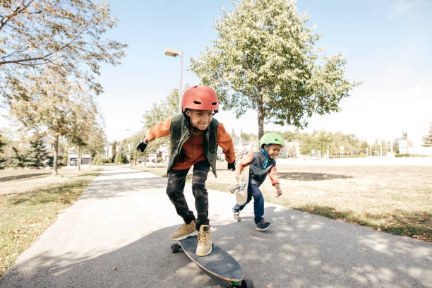 siblings having fun with longboard - skateboard stock pictures, royalty-free photos & images