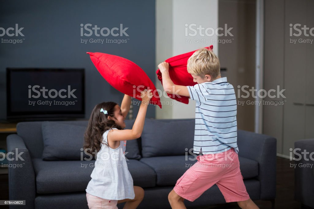 Siblings having pillow fight in living room royalty-free stock photo
