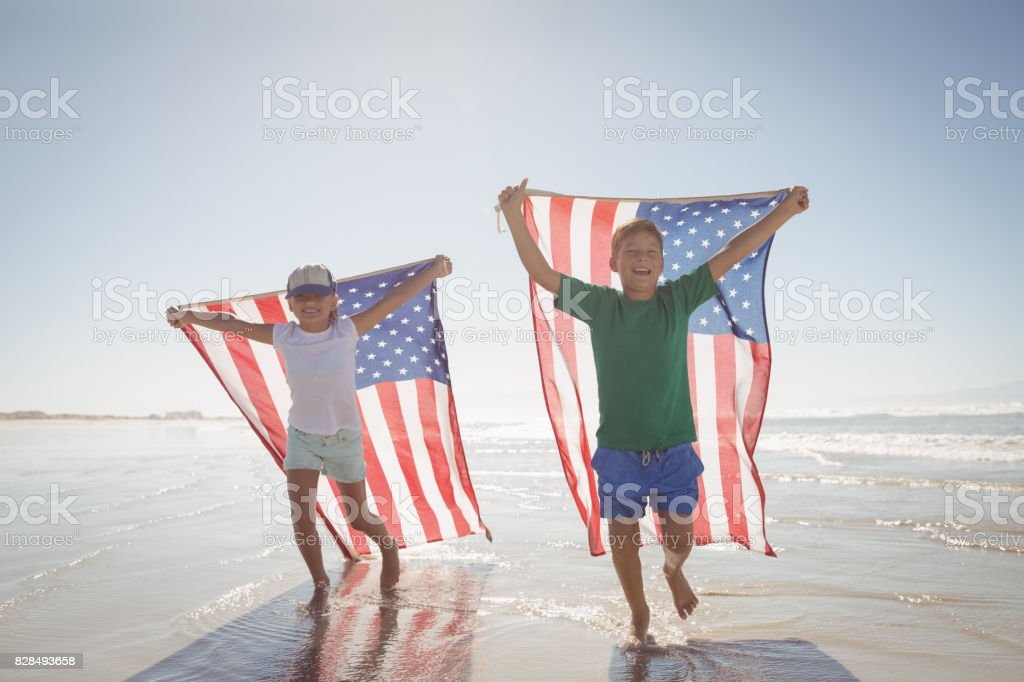 Siblings holding American flags while running at beach stock photo