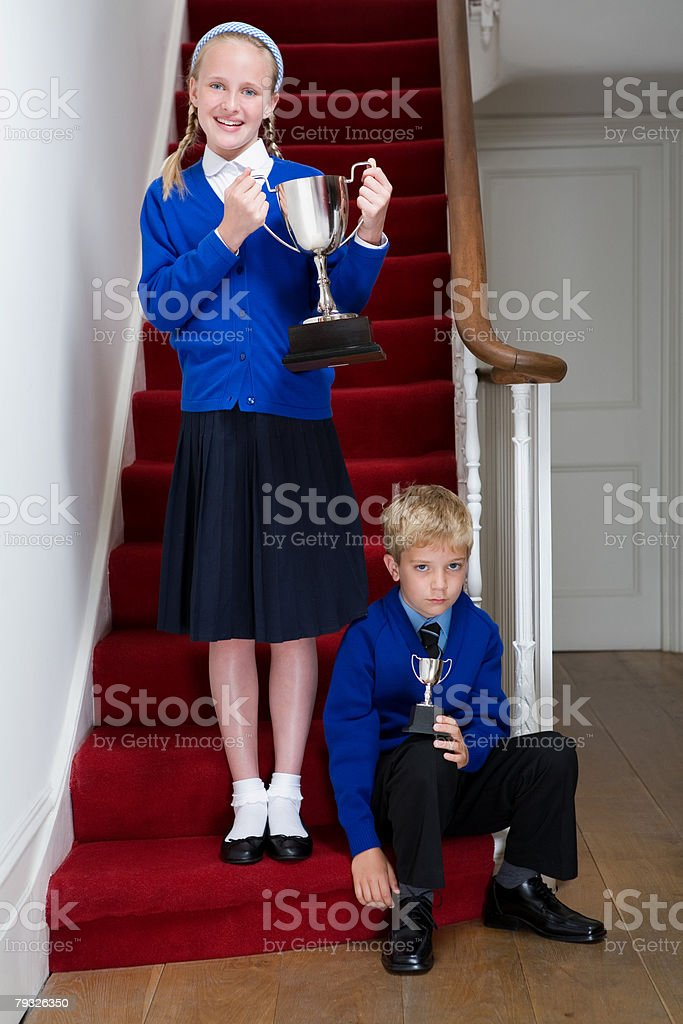 Siblings holding their trophies 免版稅 stock photo