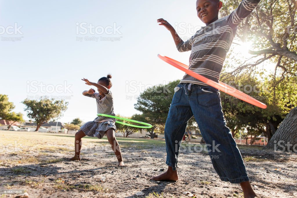 Siblings hula hooping together. stock photo