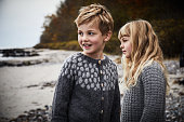 Siblings in knitwear on beach, looking away