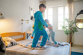 Siblings in pajamas jumping on the bed