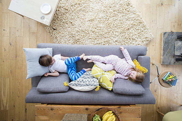 siblings on the sofa - mädchen wochenende stock-fotos und bilder