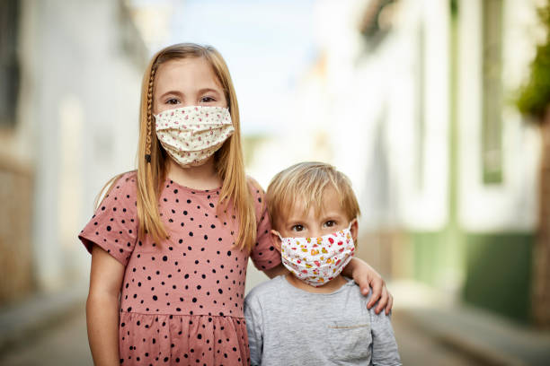 Geschwister auf der Straße mit handgefertigten Masken für COVID-19 – Foto