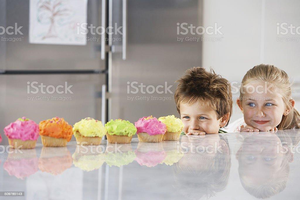 Siblings Peeking Over Counter At Row Of Cupcakes stock photo