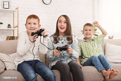Siblings playing game console while boy cheering for them on sofa