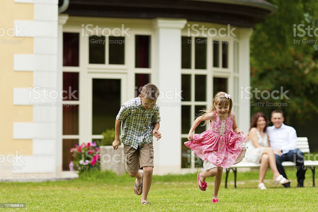 Siblings playing on front lawn while parents watch stock photo