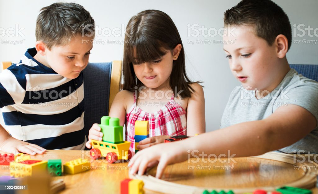 Siblings playing with blocks, trains and cars stock photo