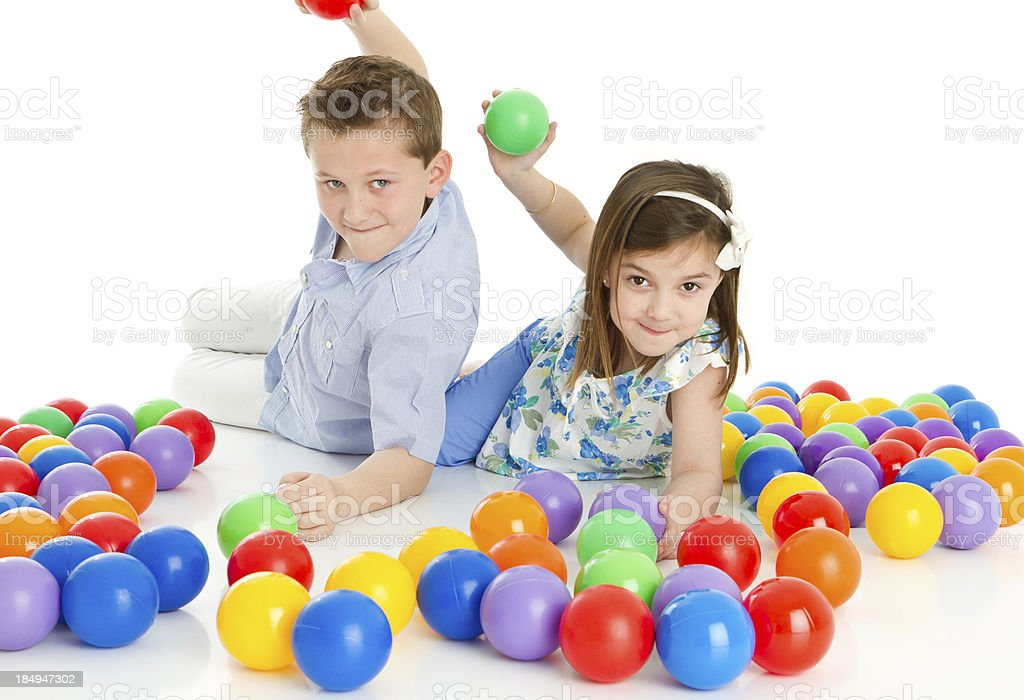 Siblings playing with colorful balls royalty-free stock photo