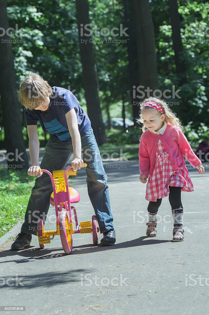 Siblings playing with pink kids tricycle on park tarmac footpath stock photo