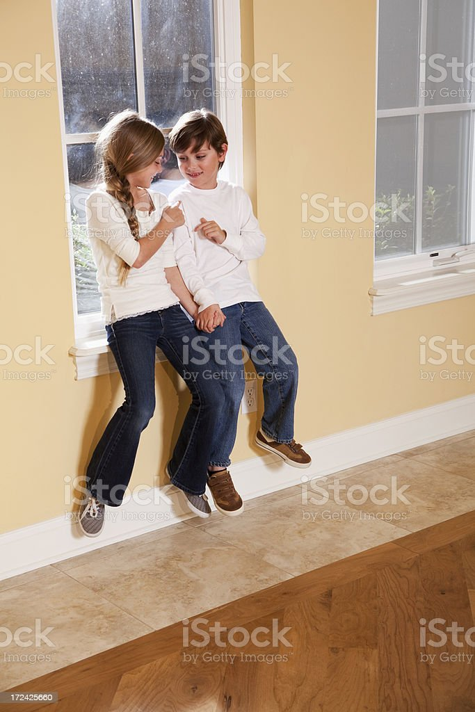 Siblings poking each other stock photo