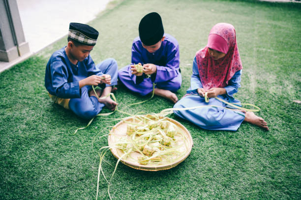 siblings preparing food in front of house - ketupat stock pictures, royalty-free photos & images