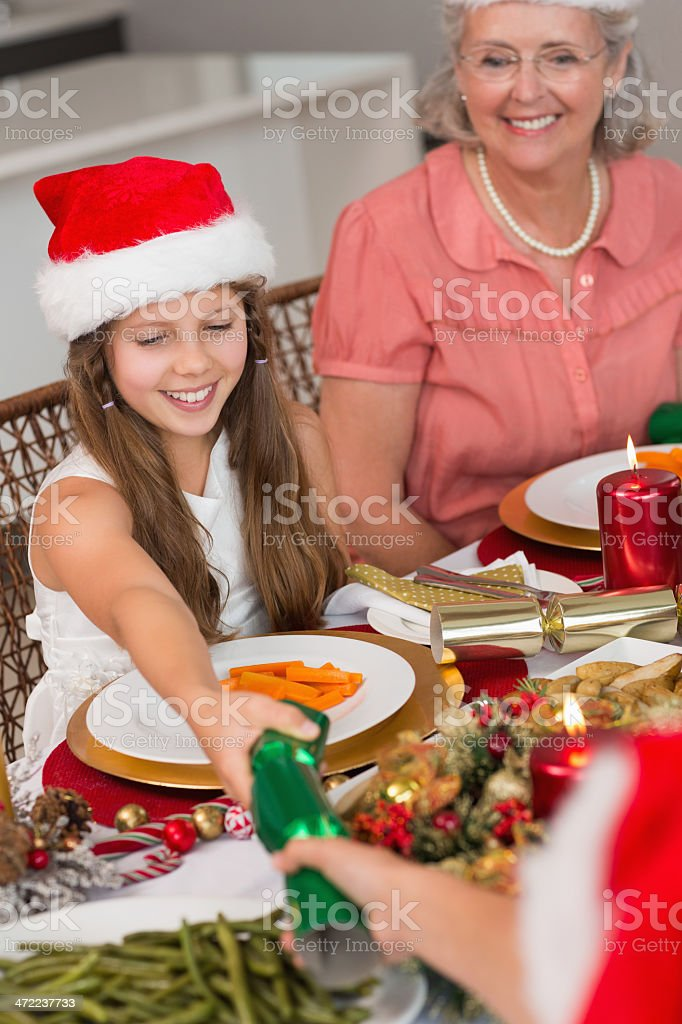 Siblings pulling Christmas crackers over dining table royalty-free stock photo