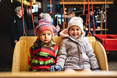Little sisters on an amusement park ride