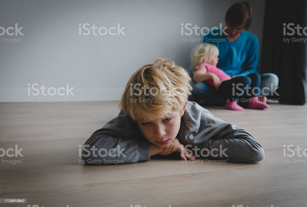 兄弟の競争 - 悲しい息子と赤ん坊の娘を保持しているパパ ストックフォト