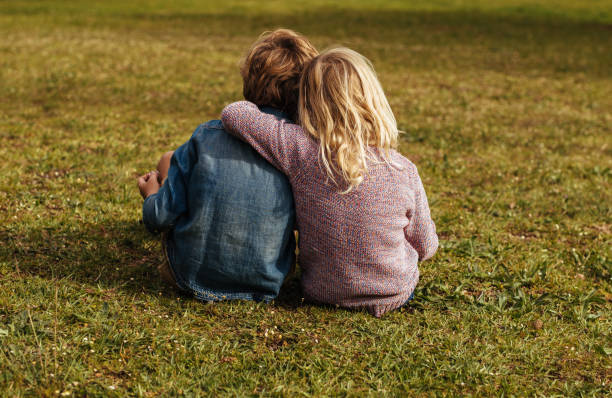 Siblings sitting on the grassy lawn Rear shot of siblings sitting on the grass. Little girl sitting with her brother putting her arm on his shoulder at park. brother stock pictures, royalty-free photos & images