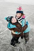 Two children are standing on the ice wearing skates and winter clothing - they are looking up and smiling while looking at the camera.