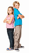 Full length portrait of siblings smiling while standing back to back. Vertical shot. Isolated on white.