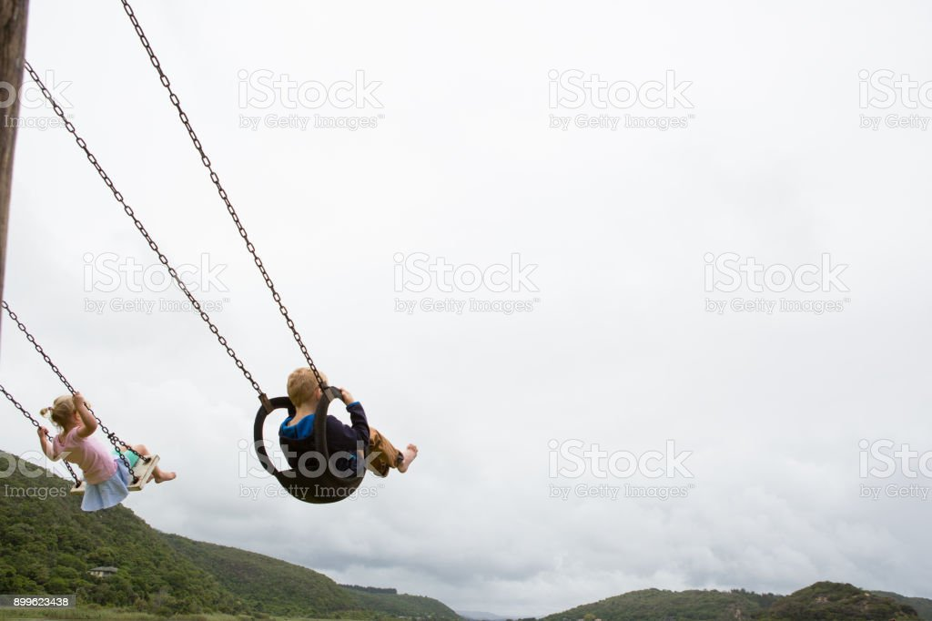 Siblings swinging on a swing together stock photo
