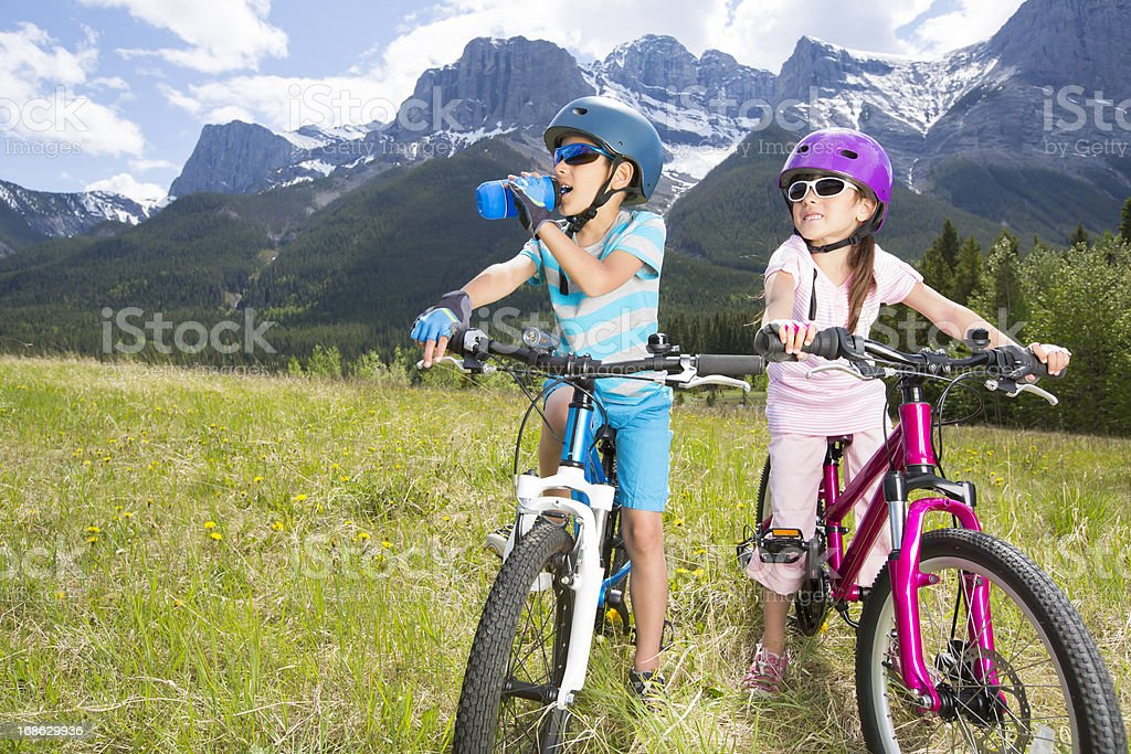 Siblings taking a break from biking to replenish royalty-free stock photo