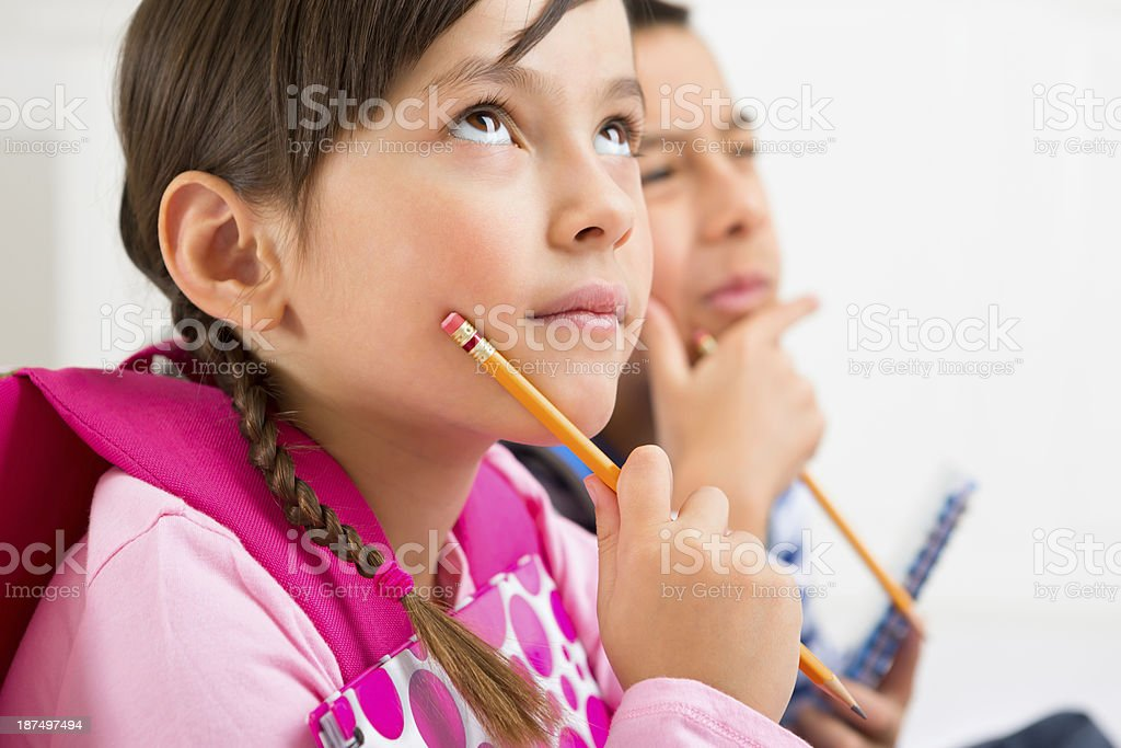 Siblings thinking about the answer to their homework royalty-free stock photo
