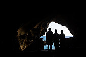 The silhouette of three young adult siblings traveling together around the world, here visiting the Hercules Cave near Tangier, Morocco.