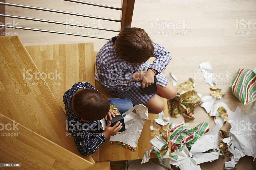 Siblings unwrapping Christmas presents stock photo
