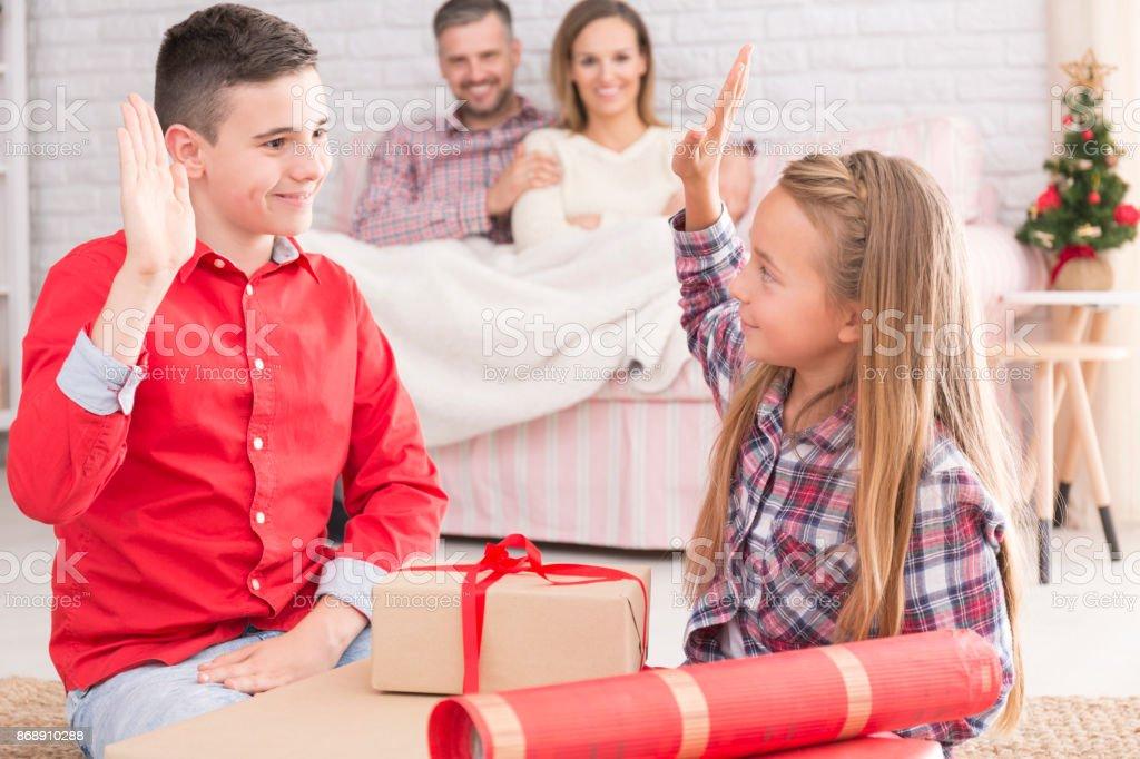 Siblings upacking gifts from Santa stock photo