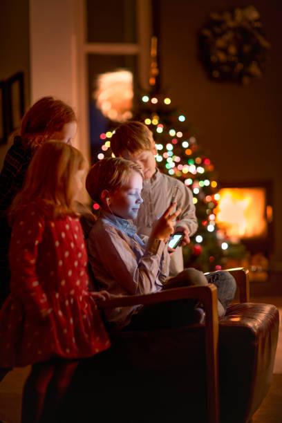 geschwister mit smartphone während der weihnachtszeit zu hause - kinder weihnachtsfilme stock-fotos und bilder