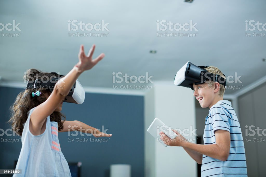 Siblings using virtual reality headset and using digital tablet in living room royalty-free stock photo