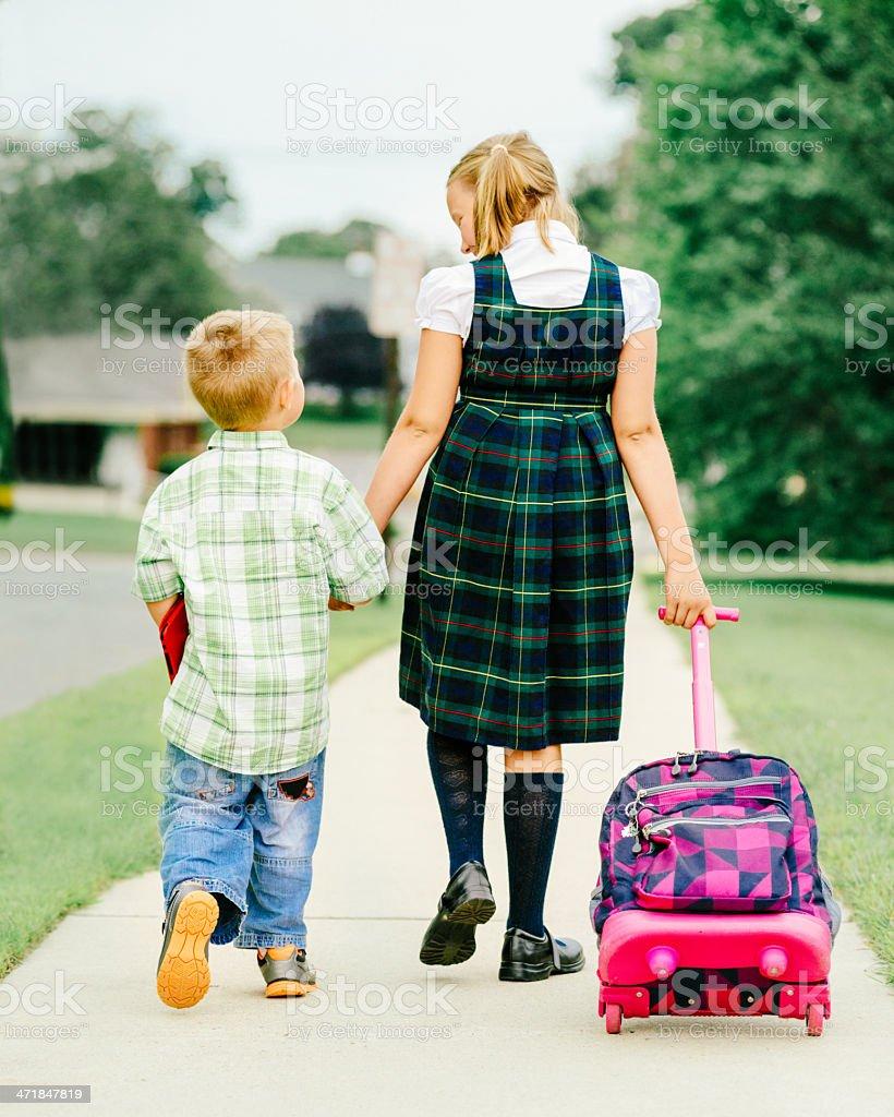 Siblings walking to school royalty-free stock photo