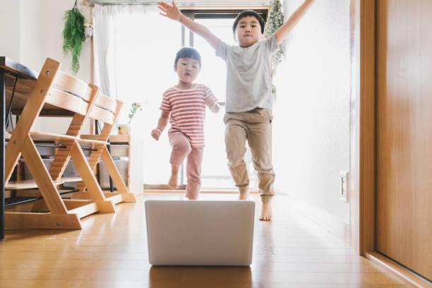 Irmãos assistindo laptop e dançando em casa - foto de acervo