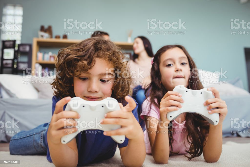 Siblings with controllers playing video game on carpet at home stock photo