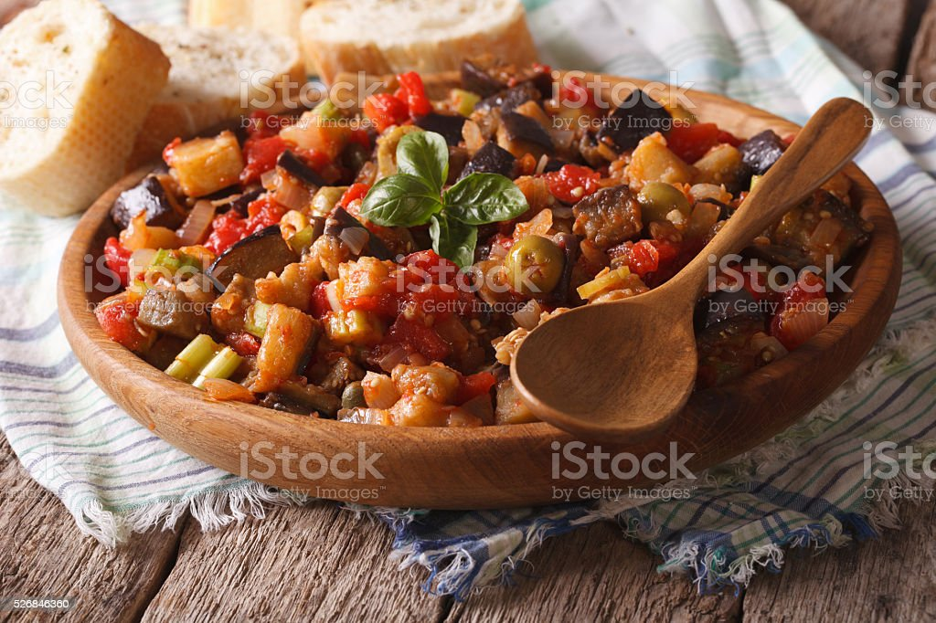 Sicilian Caponata with eggplants close-up on a plate. Horizontal stock photo