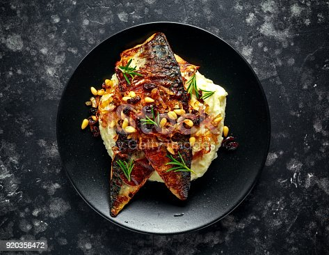 istock Sicilian style mackerel on cauliflower puree with caramelized onions, pine nuts served with rustic bread and white wine 920356472