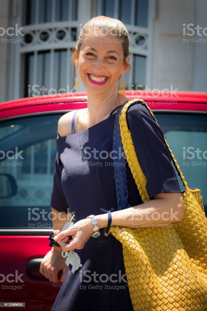 Sicily: Chic Blond Sicilian Woman Near Red Car stock photo