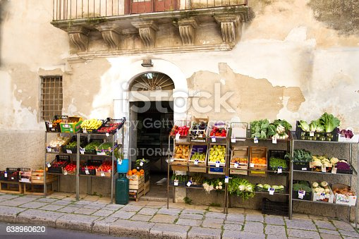 Ragusa, Sicily, Italy - April 11, 2013: Crates of fruit and veggies lined up on a cobbled sidewalk outside a colorful mini-market.
