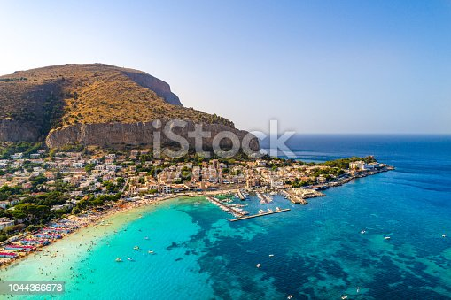 Palermo, Sicily, Italy - August 8, 2017:   view showing Sicily island, boats in the sea, trees, buildings and mountains can be seen on the background