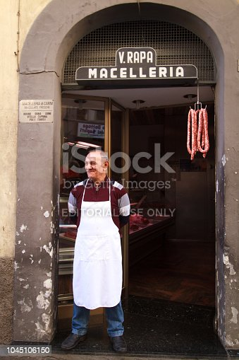 Vizzini, Sicily, Italy: A senior butcher stands in the doorway of his butcher shop in the center of Vizzini, a town in the Catania region of Sicily. Sausages hang nearby.