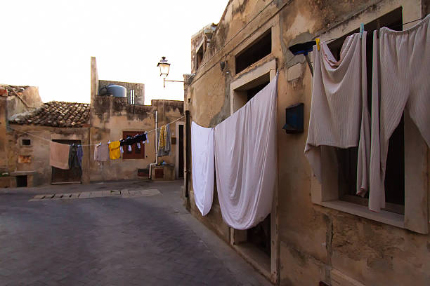 sicily scene: small old piazza with sheets and laundry - waschplätze stock-fotos und bilder